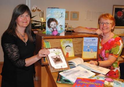 Barnebøker i skattekiste; f.v.: Kristin Havstad og Mari Senumstad Hauge ved Aust-Agder bibliotek og kulturformidling. Foto: Rune Kristiansen